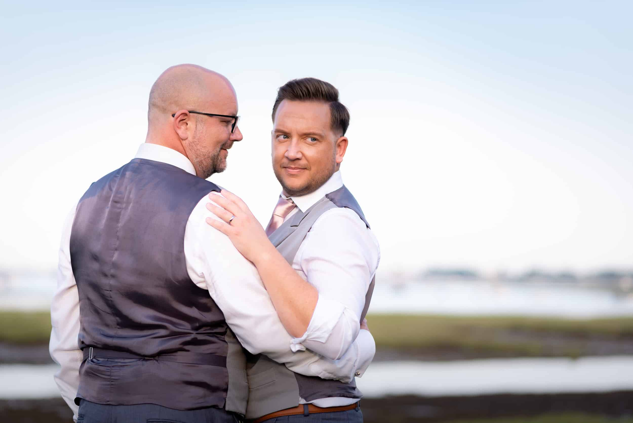 Gay couple on their wedding day having some loving and natural shots by the sea at Two Woods estate in Essex