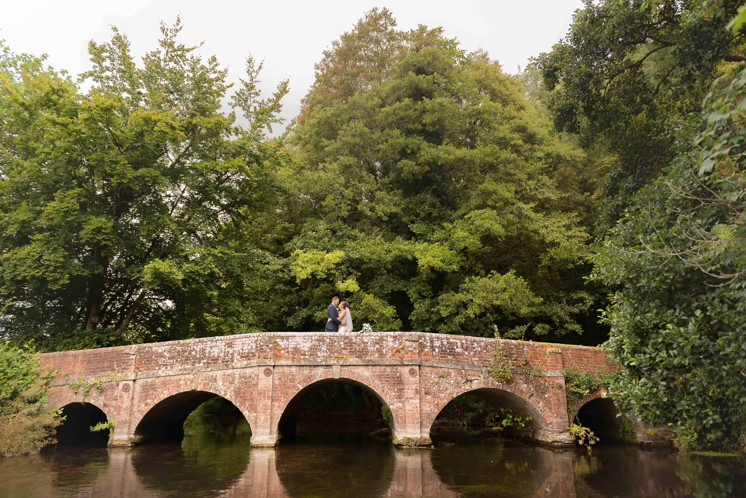 Beautiful Landscape photo of a bride and groom stood on a bride looking lovingly at each other, beautiful trees in the background and river in the foreground, in Salisbury, Wiltshire
