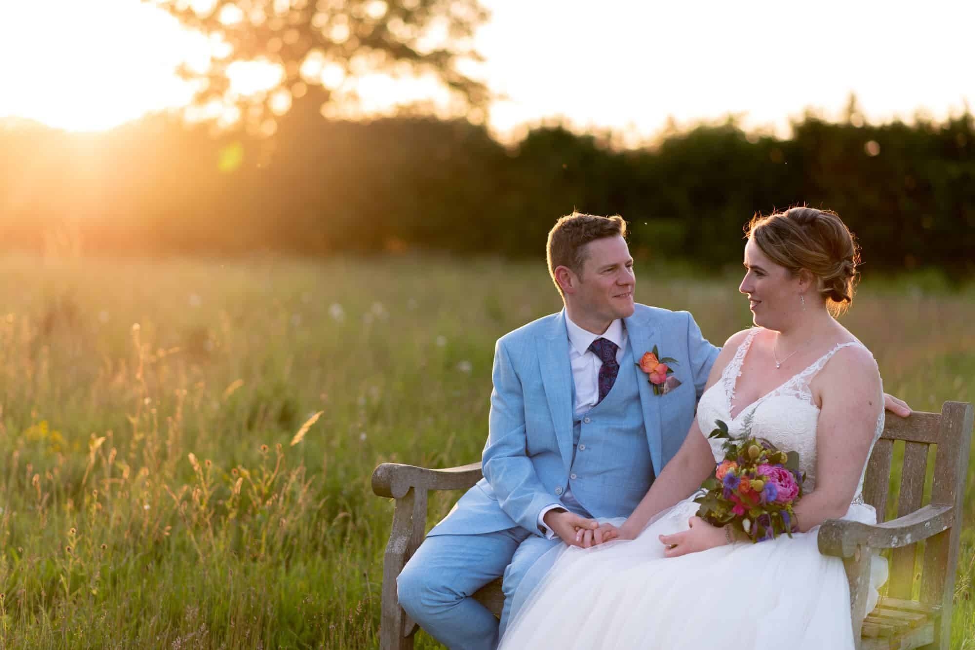 Sunset wedding photos at hawk Conservancy in Andover. Sat on a bench together for some relaxed and fun photos of their wedding day. Such a romantic shot