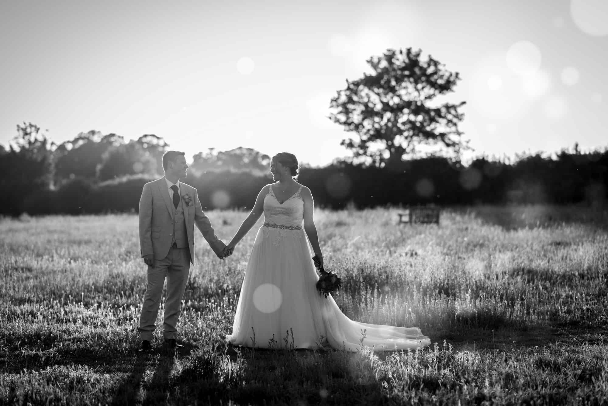 Couple holding hands at sunset. black and white photo at Hawk Conservancy in Andover on their wedding day