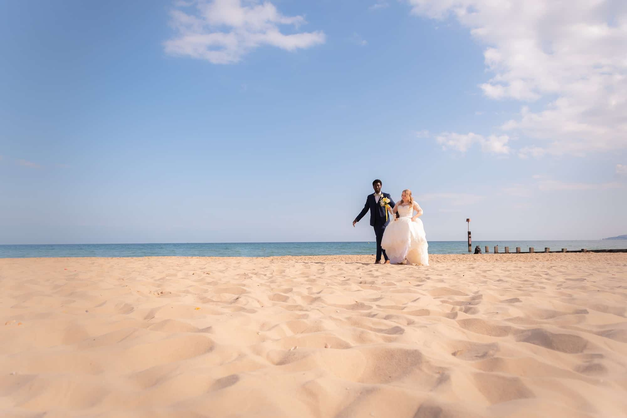 bride and groom having couple shots are their wedding ceremony on Bournemouth Beach in Hampshire. Walking along the sand, holding hands on a bright and sunny day in Hampshire