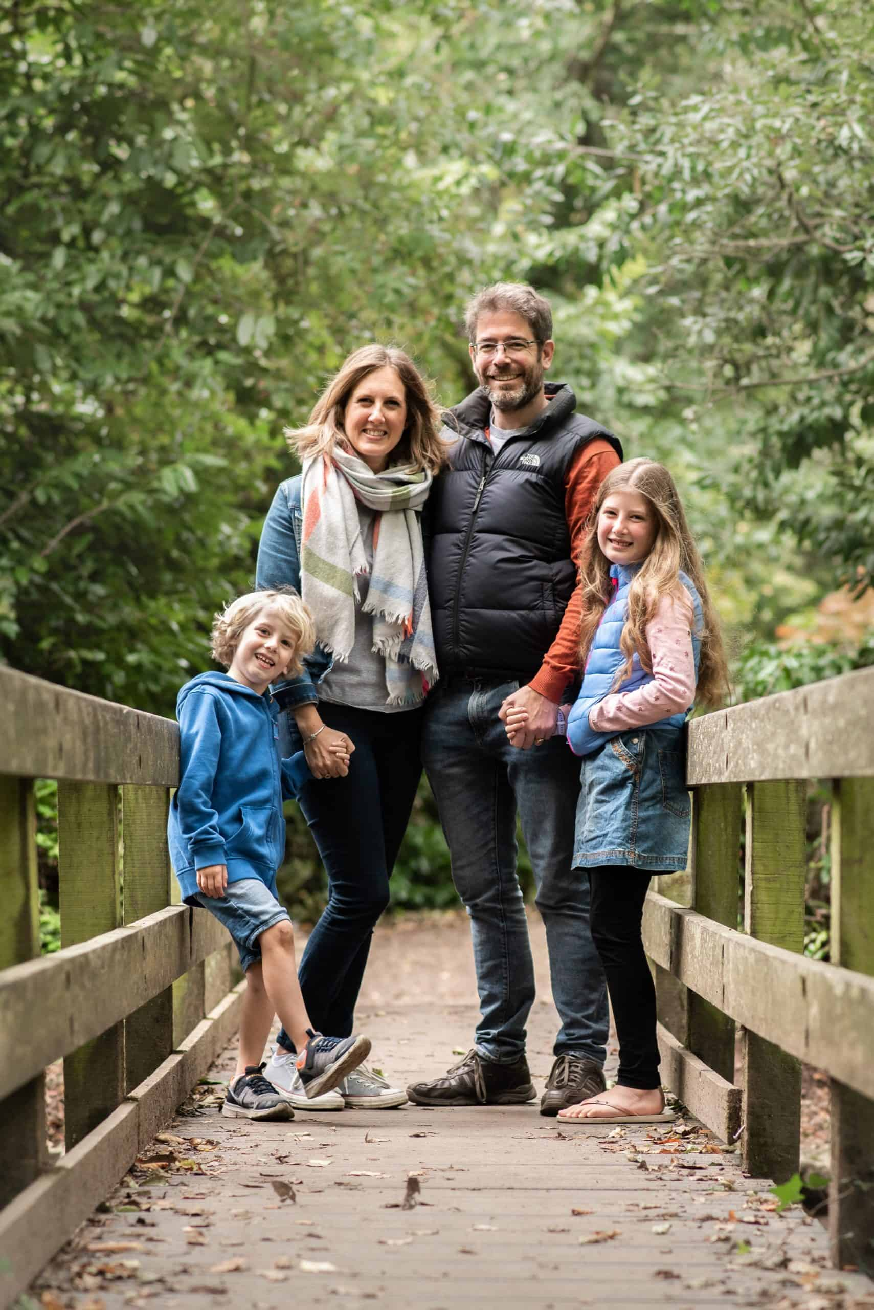 Fun family photo shoot stood on a bridge at holly hill Sarisbury Green, hampshire. holding hands and looking at the camera together with mum & Dad and the children