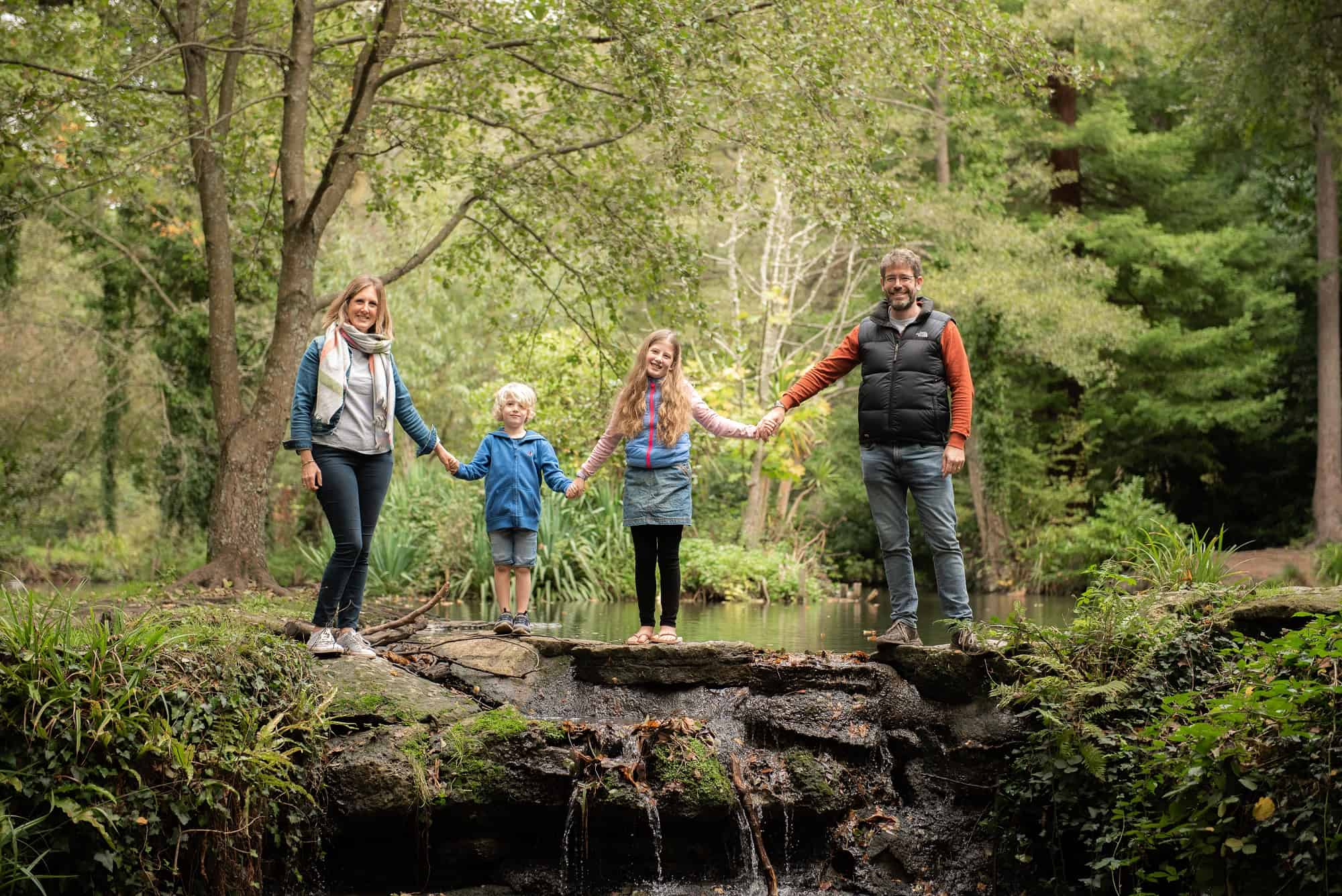Family having a photo shoot at Holly hill in sarisbury green, southampton. holding hands over a small waterfall in a line together