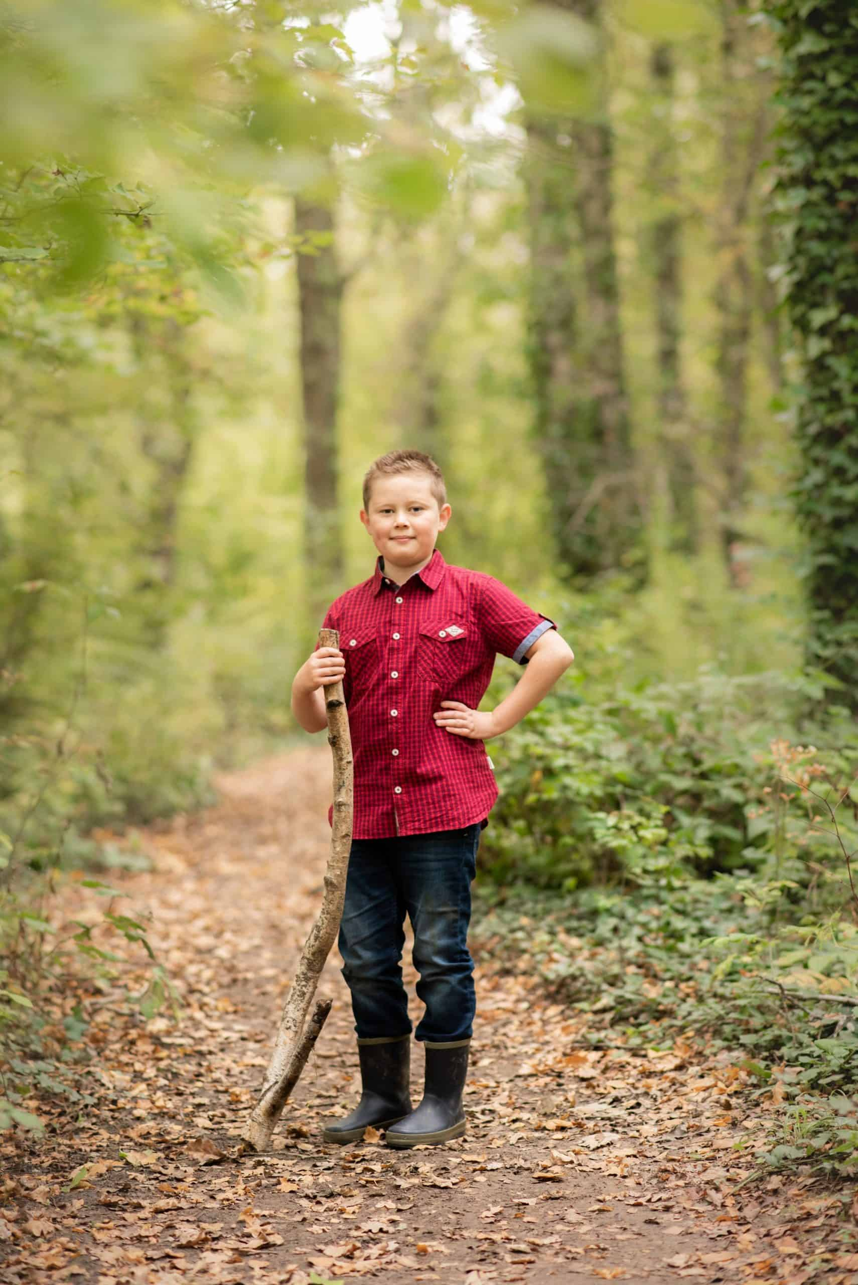 Young boy stoff in the woods posing for a photo oh him for his mum and dad
