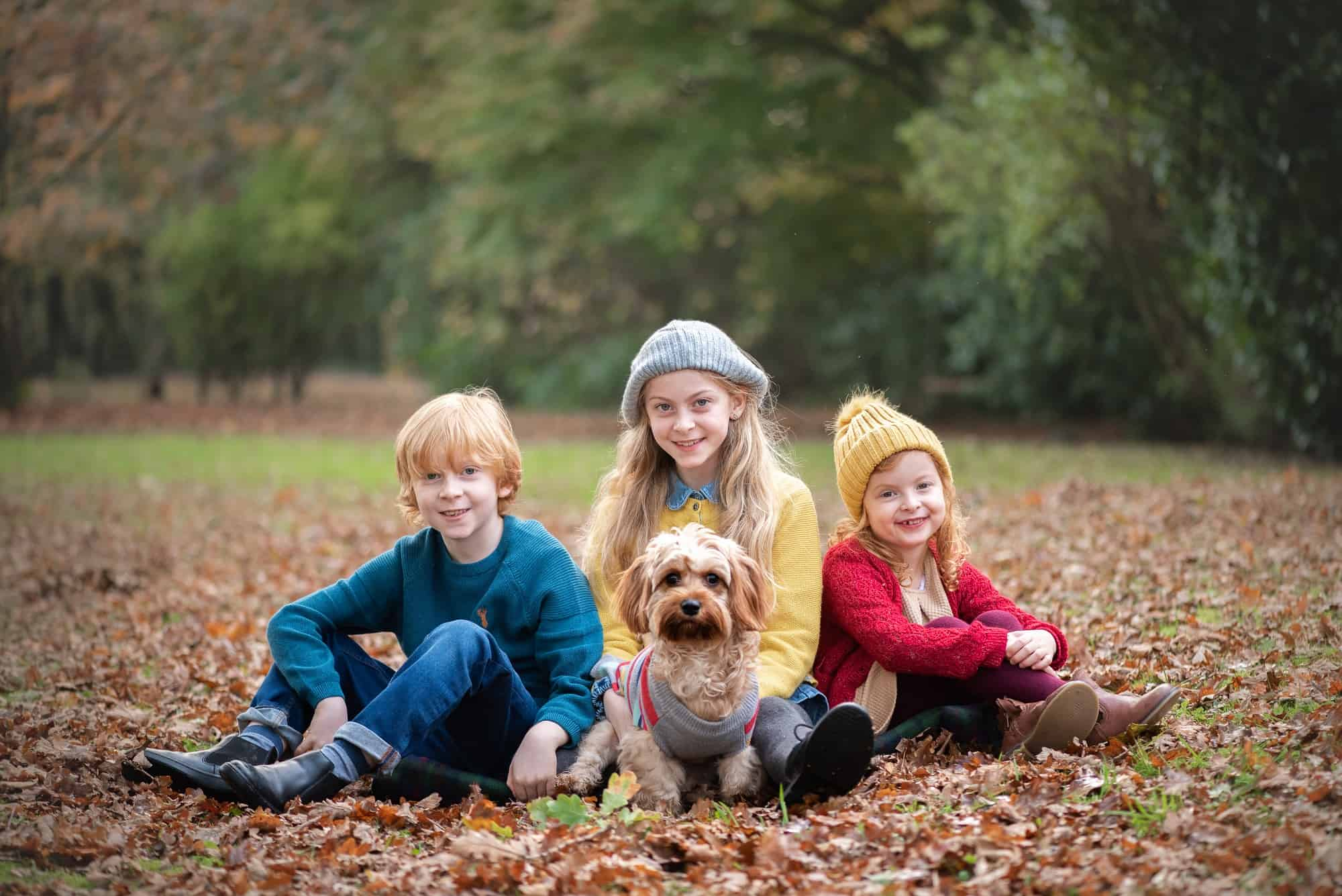 Fun family photographer hired in Southampton hampshire of three childen sat posed for family photo with their puppy. in their own garden, during the autumn