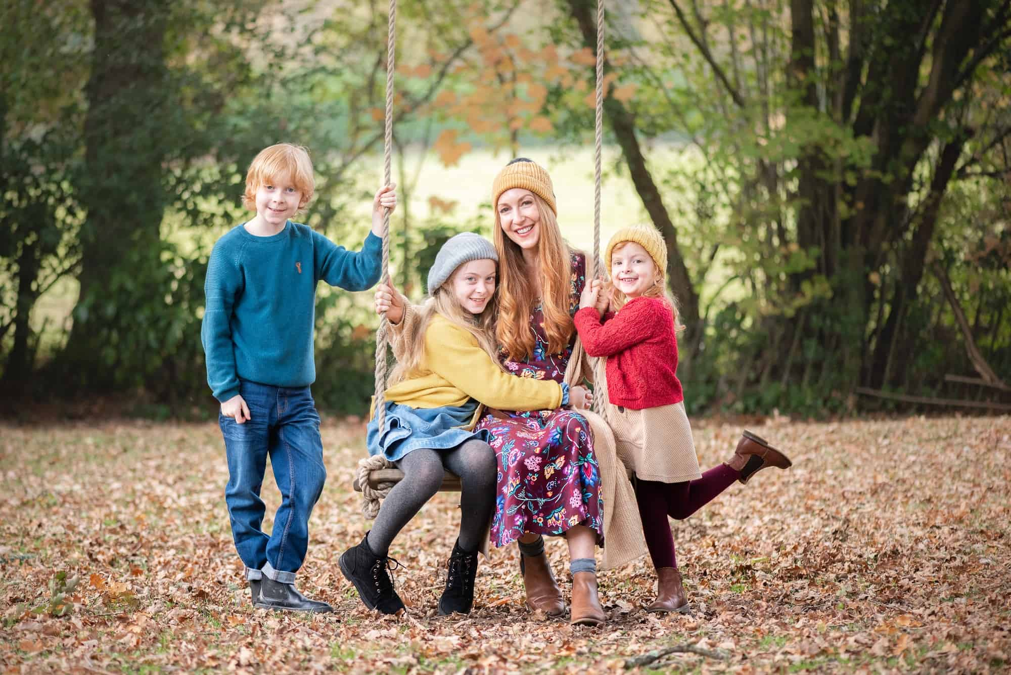 Mother and her children sat on a swing and gathered round, posing for the fun family photo session near Botley, Eastleigh. In their garden