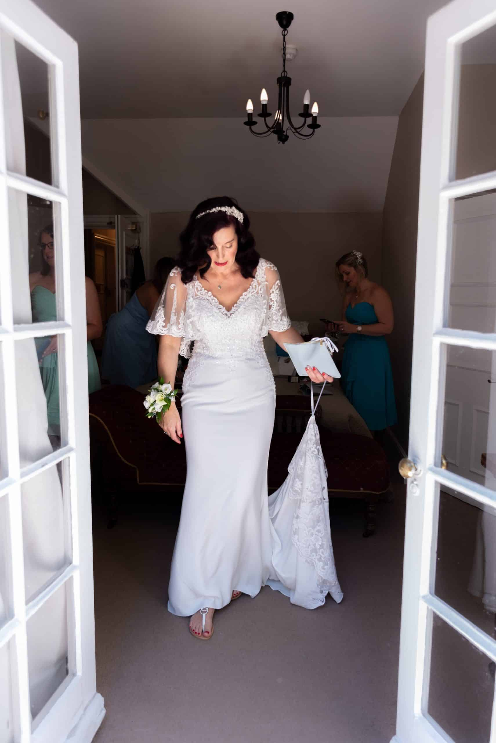 Portrait of bride standing by french doors looking down at hre wedding dress