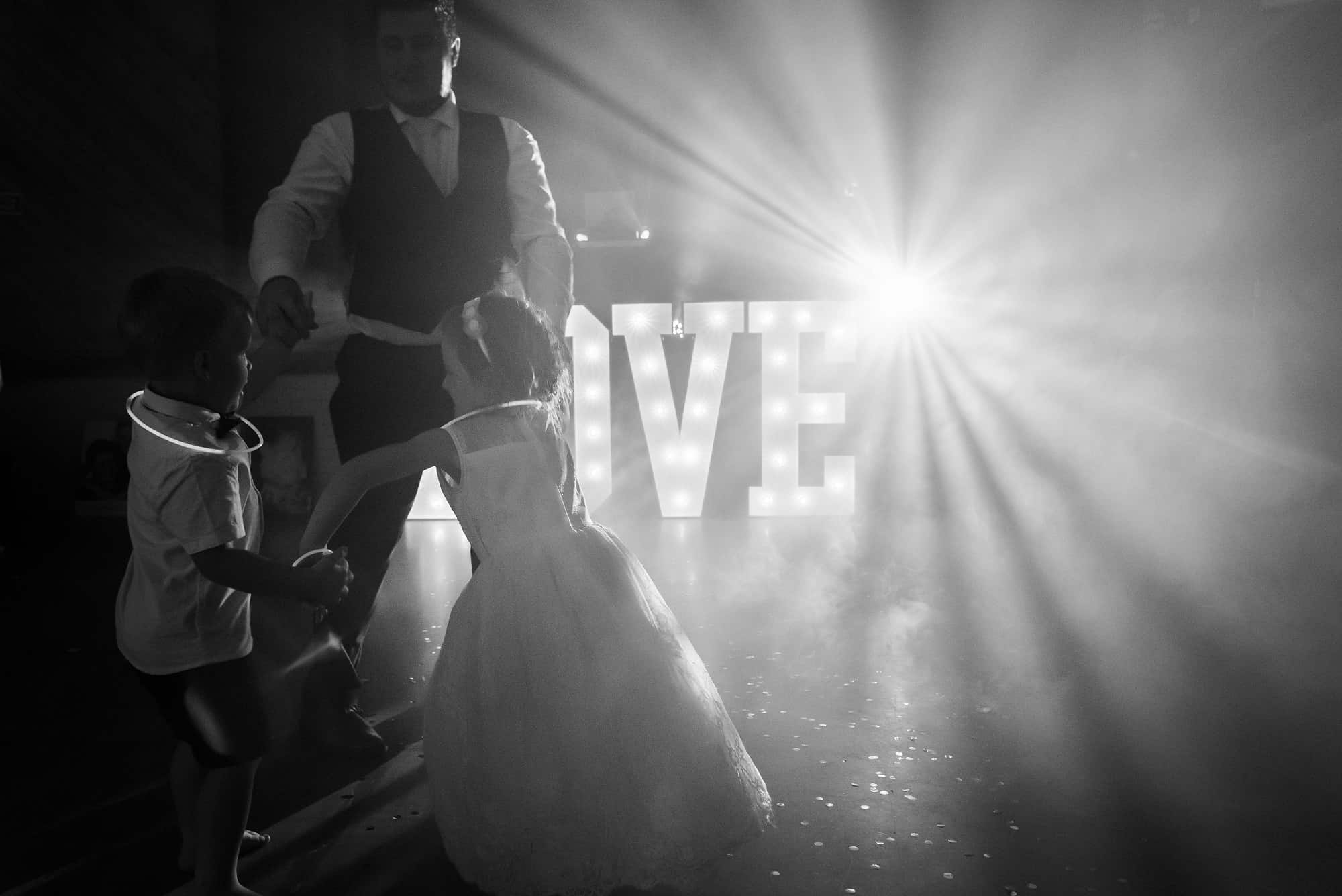 Black and white photo of Groom dancing with children at the reception of their wedding. Lights in the background and a love sign in the background