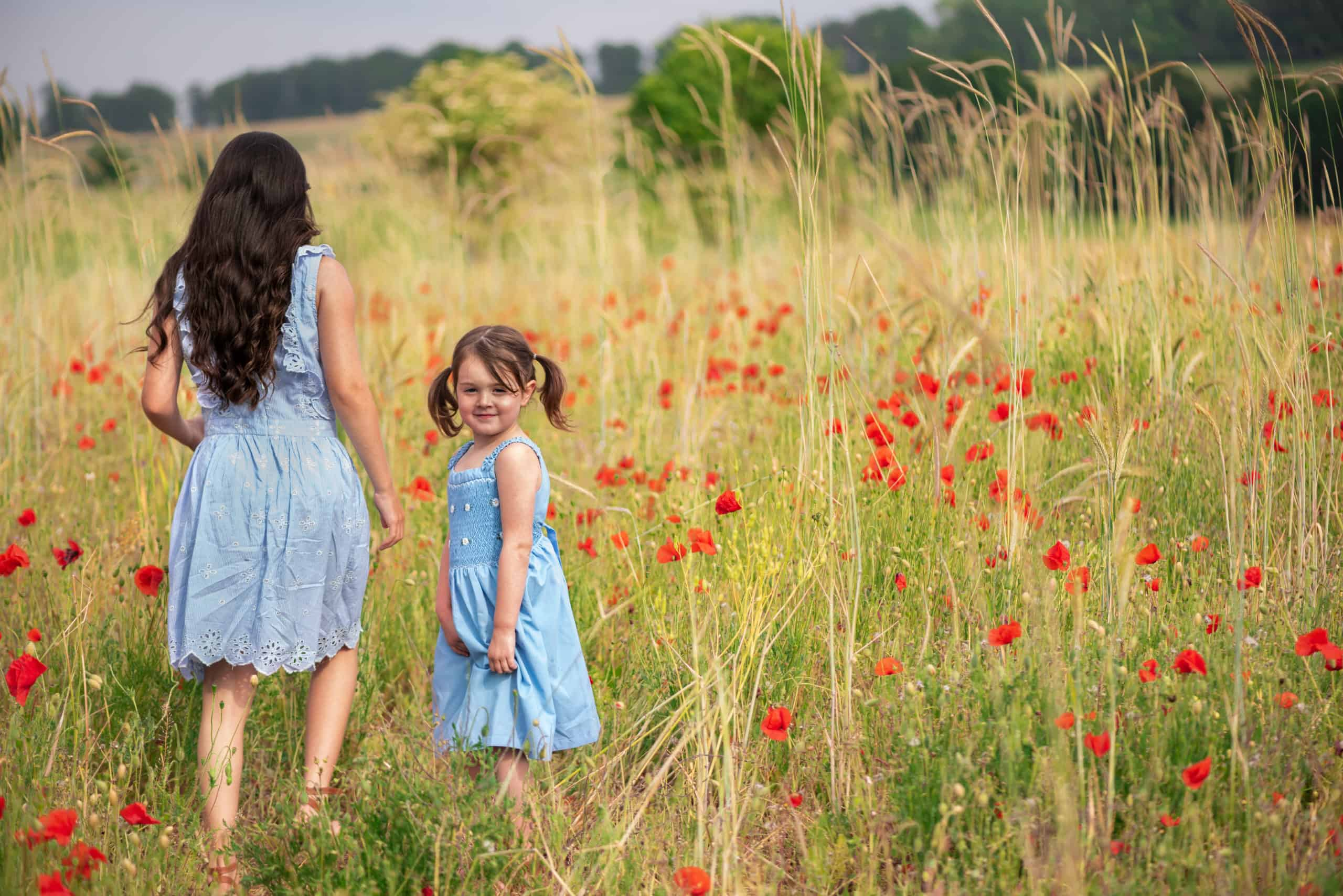 childrens portraits in pop fields, two sisters together walknig hand in hand at twyford, near winchester