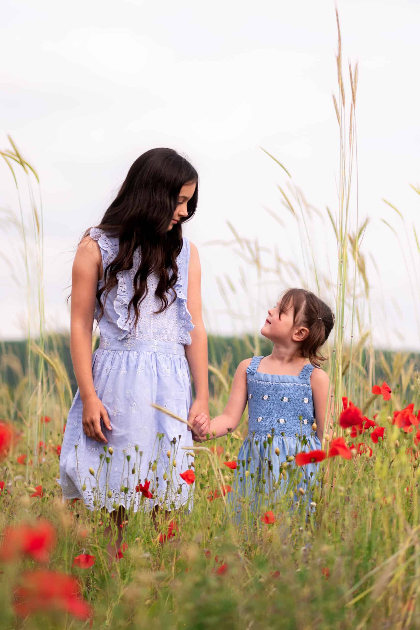 Poppy field with two girls, sisters looking at each and stood holding hands.