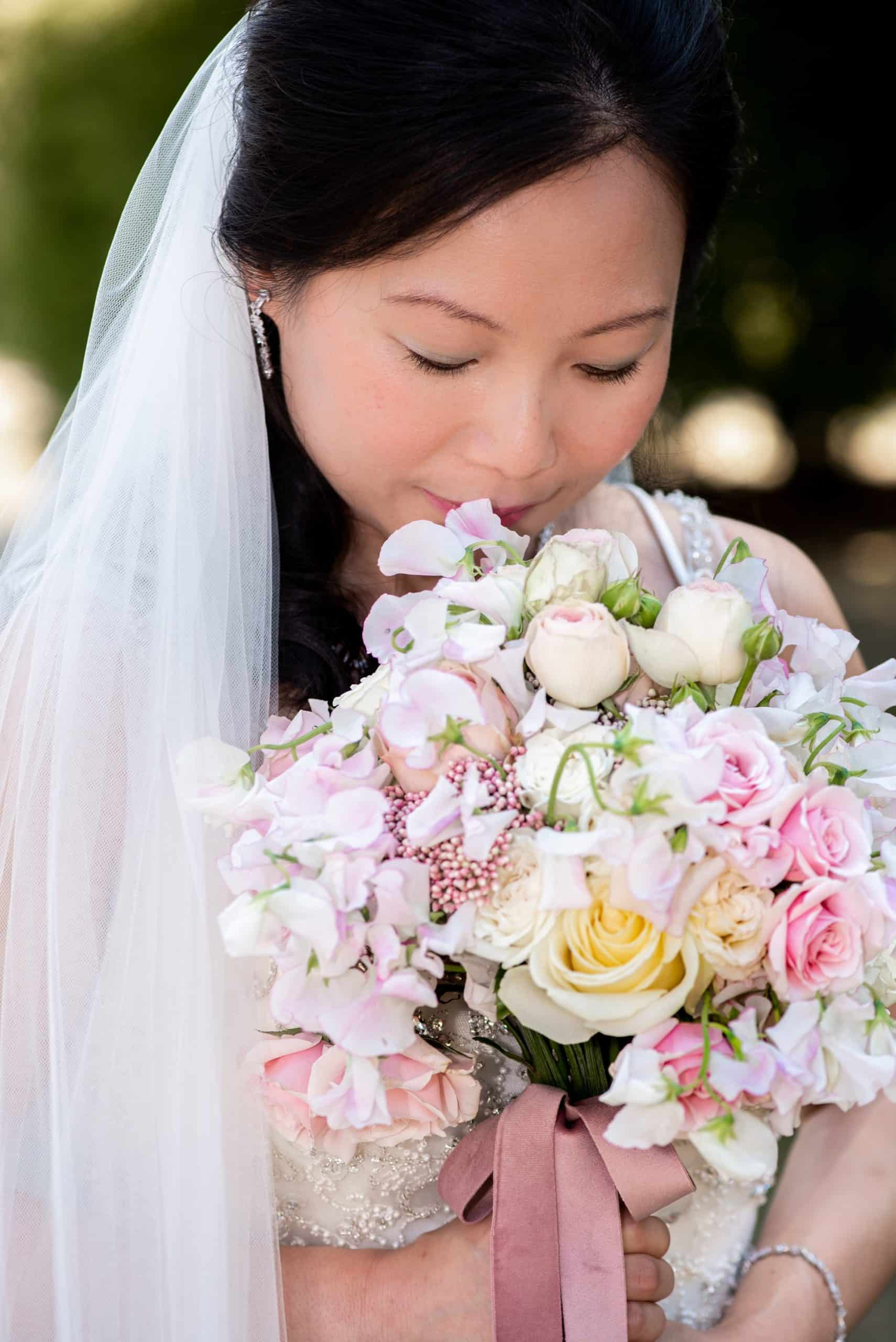 Bride holding her bouquet smiling, light and airy wedding photo