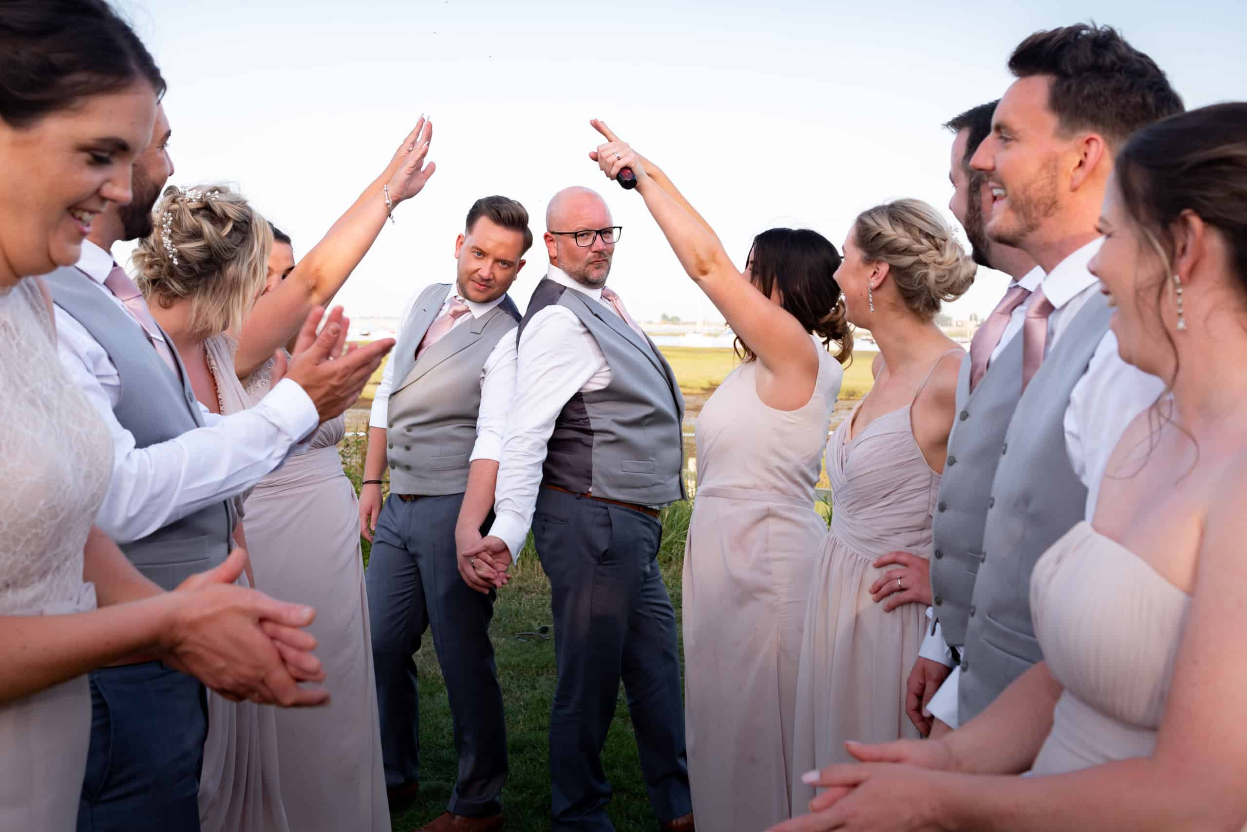Gay couple at their wedding taking photos with their party