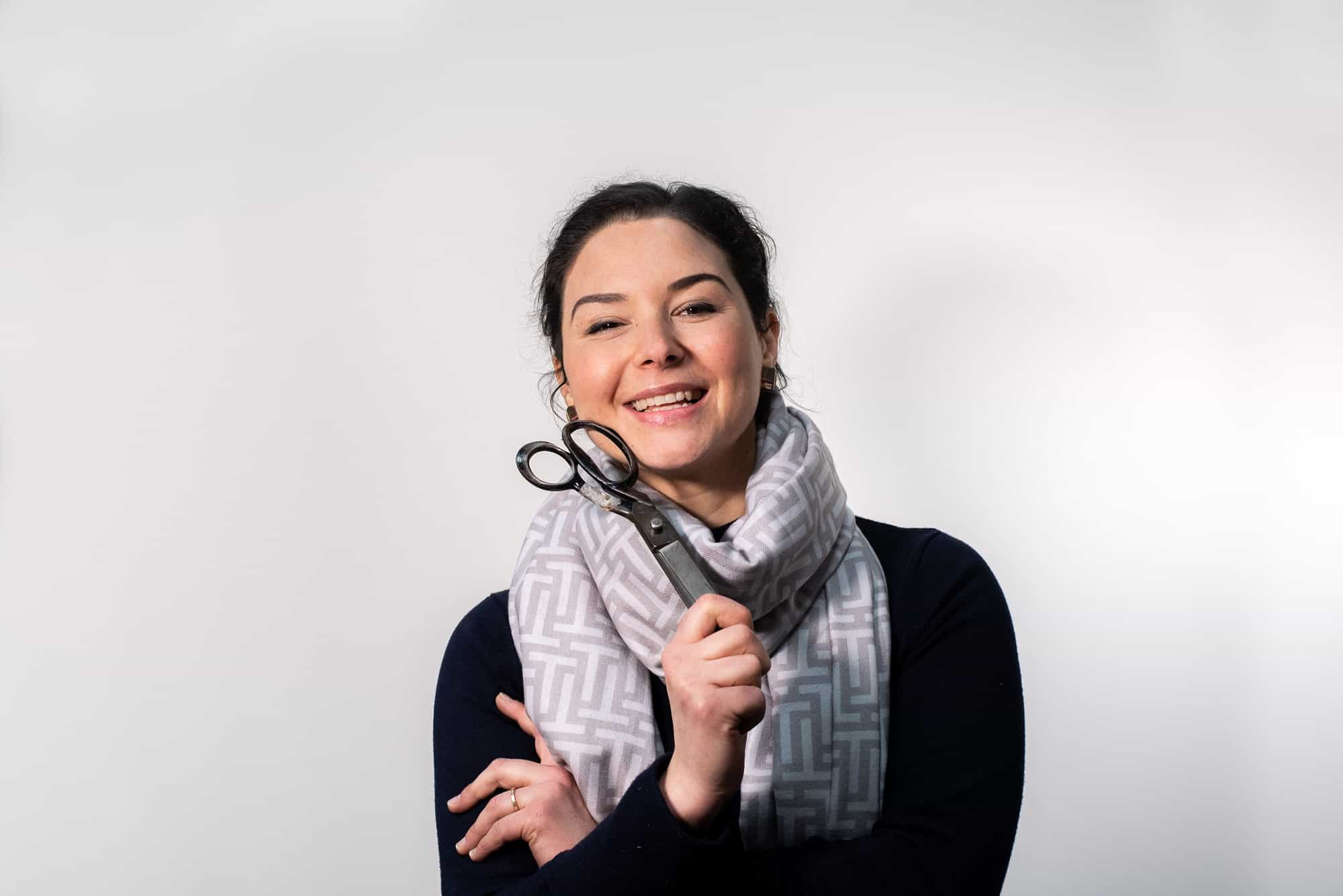 relaxed fun portrait for her business smiling at camera holding some scissors from her upholstery business