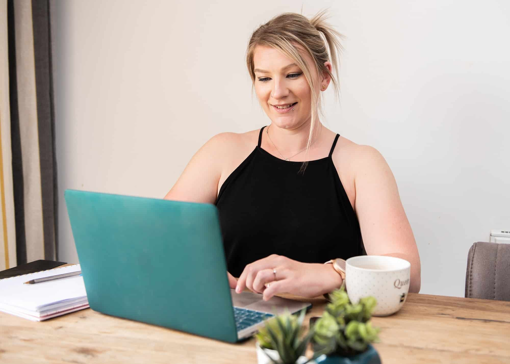 business portrait od lady sat at desk on her laptop