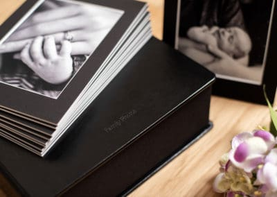 Bespoke mounted prints in balck faux leather box with nikon camera to the side, hands holding some prints